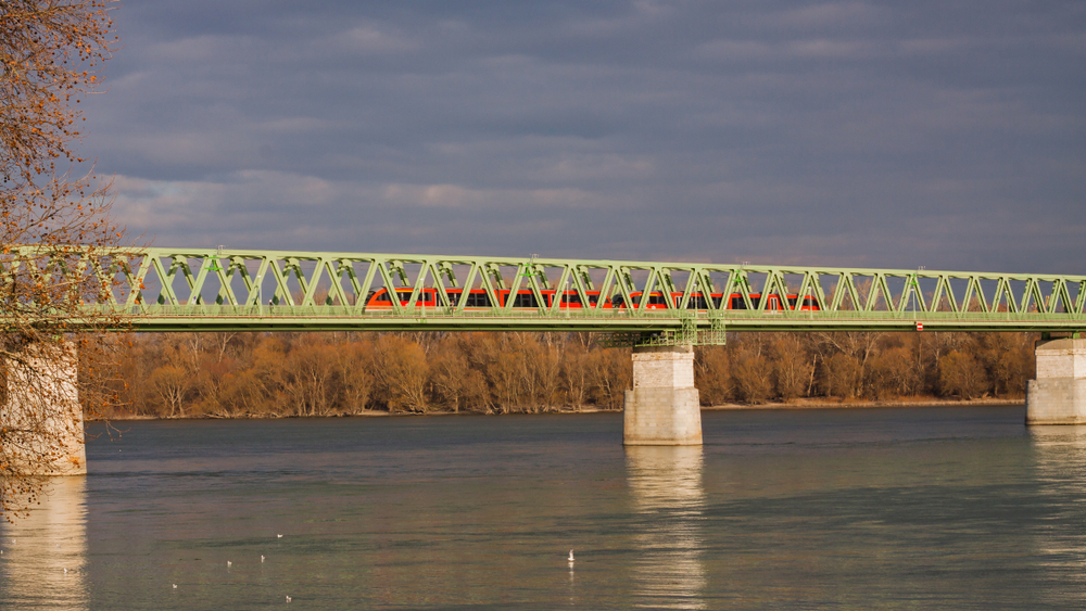 Red train crossing the railway bridge over the river Danube in Budapes
