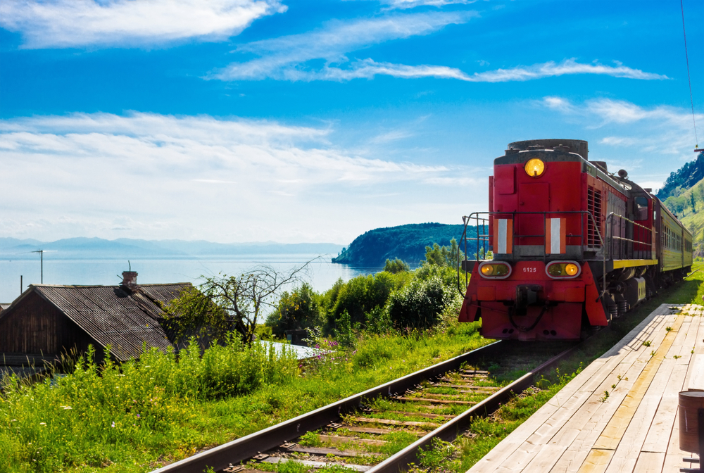 Summer landscape with the arrival of a red train on a wooden empty platform Trans-Siberian railway in village on shore Lake Baika
